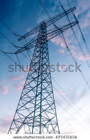 A birds-eye view of an electricity pylon against a twilight sky
