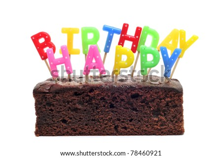 a birthday cake with candles forming the sentence happy birthday on a white background - stock photo