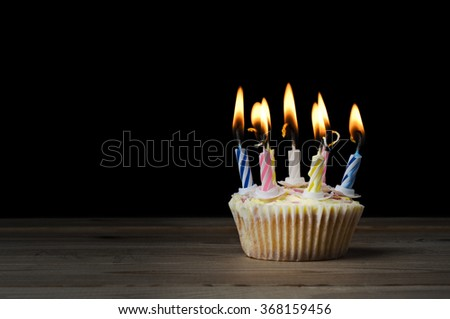 A birthday cupcake in a  plain paper case with seven striped, lit candles on a wooden table with black background. - stock photo