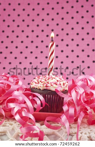 A birthday cupcake with one lit candle, selective focus, low key