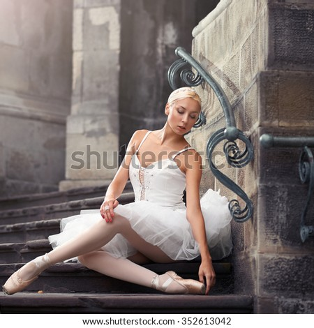 A bit of rest for the prima. Gorgeous ballerina sitting on an old stairway looking away  - stock photo