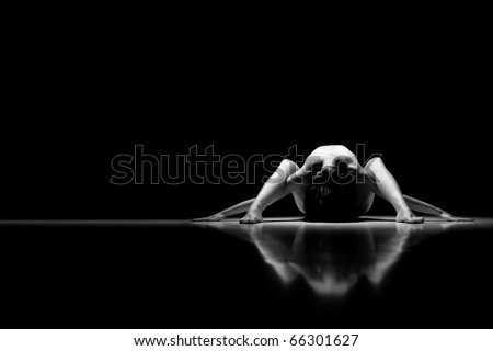 a black and white artistic nude of a woman, shot on black background. the arms and legs are streched to the horizontal and the head is bent down. - stock photo