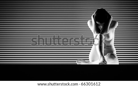 a black and white artistic nude of a woman, shot on striped background. she is sitting down with one knee up, both her elbows joined with the knee and her hands on her head. - stock photo