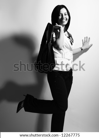 A black and white high-key portrait about a beautiful trendy girl with black hair who is smiling, she is having fun and she has an charming look. She is wearing black pants, and a white coat.