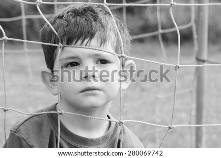 A black and white image of a little boy with his face in a net. He is making a serious and thoughtful face. Close up. Horizontal.  - stock photo