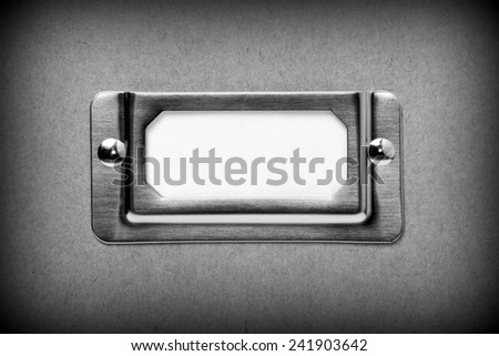 A black and white image of a metal drawer label holder with a blank white index card for copy space. A vignette has been added for effect. - stock photo