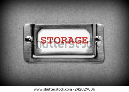 A black and white image of a metal drawer label holder with a white index card and the title Storage added in red text