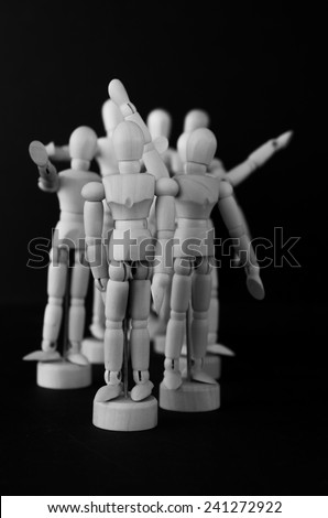 A black and white image of artist's manikins with upraised arms to signify waving, anger, happiness or cheering - stock photo