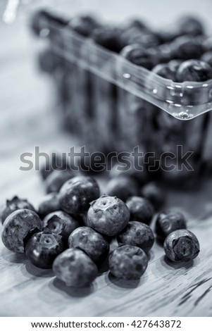 A black and white image of fresh blueberries from a farmer's market are on the counter ready for consumption. - stock photo
