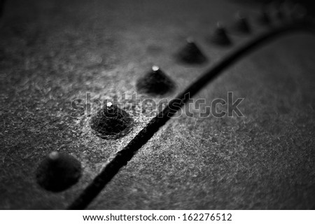 A black and white image of industrial rivets and rusty steel - stock photo