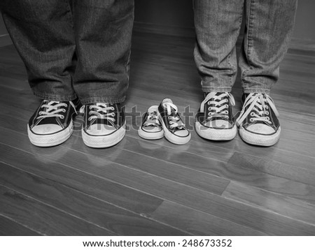 A black and white image of the feet of a man and woman wearing jeans and matching sneakers with a pair of baby sneakers between them