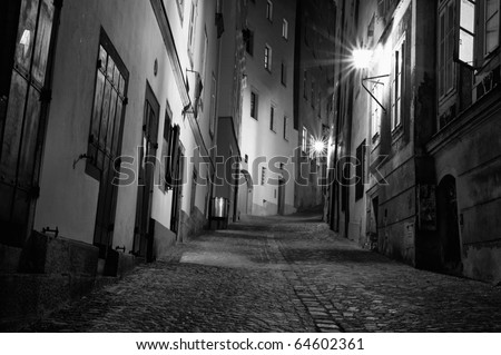 A black and white of a dark European alleyway at night in horizontal - stock photo