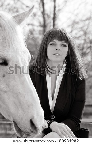 A black and white photo of an attractive brunette woman sitting on a fence in formal horse riding clothes, petting her white horse and looking strong and confident - stock photo