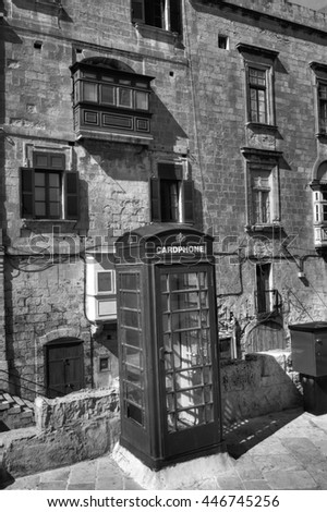 A black and white photo of an old cardphone booth in the historic city Valletta with an old appartment building in the background