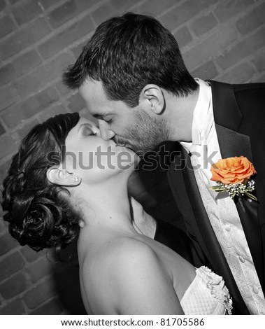 A black and white photo with color accent of a bride and groom kissing after being pronounced man and wife.