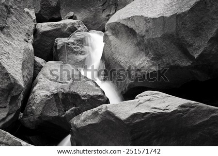 A black and white photograph of water streaming down rocks at Yosemite Falls in Yosemite National Park. - stock photo