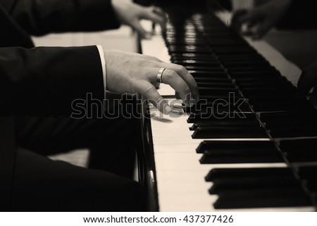 A black and white picture of a man playing on the piano