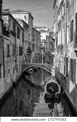 A black and white portrait image of a canal in Venice, Italy with boats moored along the side. A foot bridge is seen and is reflected in the still water
