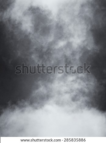 A black and white rendition of fog and clouds on a textured paper background.  Image displays a distinct paper grain and texture at 100 percent. - stock photo