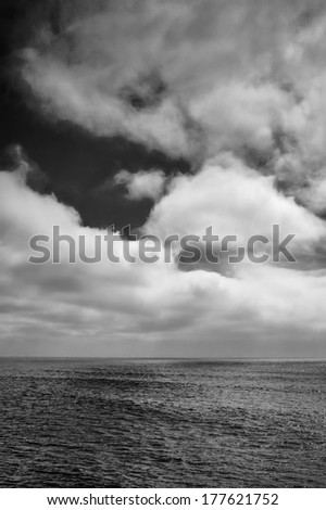 A black and white shot looking out to the Pacific Ocean just after a storm. - stock photo