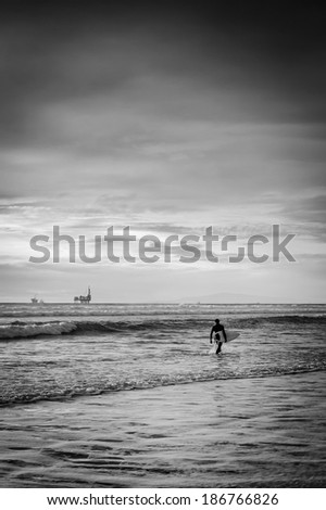 A black and white shot of a surfer walking on the beach looking for a good set of waves.