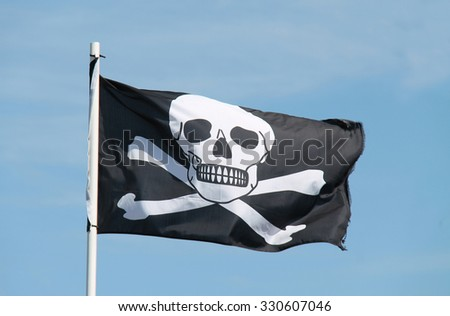 A Black and White Skull and Cross Bones Pirate Flag. - stock photo