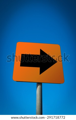 A black arrow red sign pointing to the right against blue sky - stock photo