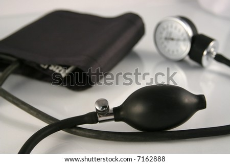 A black blood pressure monitor on a gray background - stock photo
