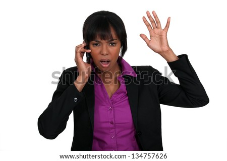 A black businesswoman angry over the phone. - stock photo