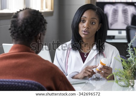 A black female physician prescribing pills to an older black male patient - stock photo