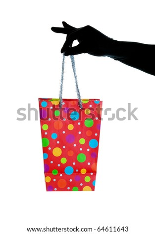 A black gloved hand holding a Christmas gift bag with glitzy, silver tinsel handles.  Shot on white background. - stock photo