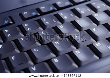 A black keyboard illuminated by the computer screen. Selective Focus. - stock photo