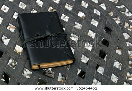 A black leather bound writer's journal tied closed with a leather cord to protect the pages outside on table with runic bookmark. - stock photo