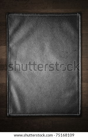 A black leather texture isolated on the wooden background. - stock photo