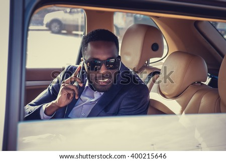A black man talking by smartphone in the car. - stock photo
