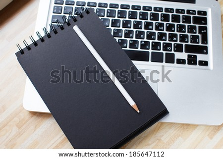 A black notepad and a white pencil on a laptop