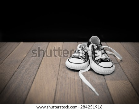 A black pair of baby sneakers sitting on a wooden floor against a black background