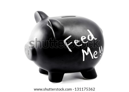 A black piggy bank isolated against a white background with the words Feed - stock photo