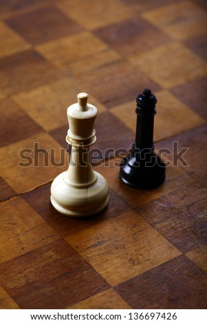 A black queen and a white king on a chess board