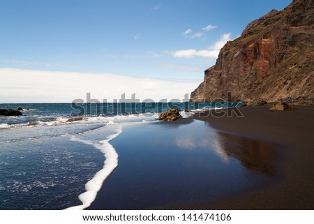 A black sand beach at the atlantic ocean at La Gomera, one of the canary islands. The sky is mirrored in the wet sand. - stock photo