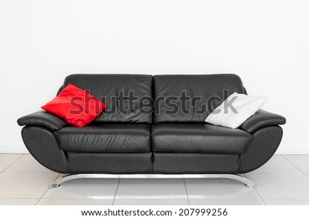 A black sofa with red and white cushion - stock photo