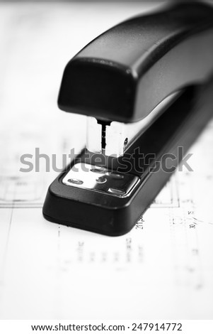 a black stapler a draft on paper - stock photo