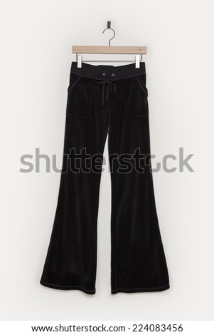 A black trousers (bell-bottoms style) with wooden hanger isolated white background. - stock photo
