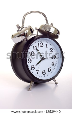 A black, vintage looking alarm clock on white background