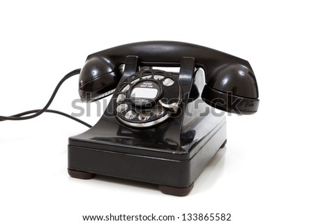 A black vintage rotary phone on a white background - stock photo