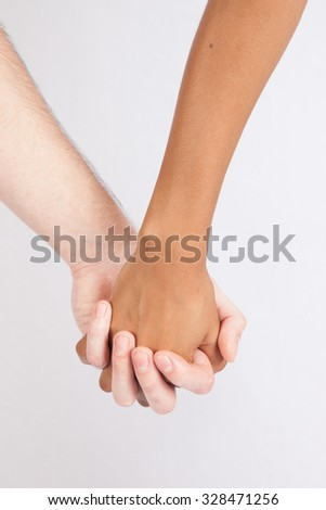 A black woman and white man holding hands