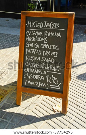 a blackboard menu on a restaurant terrace - stock photo