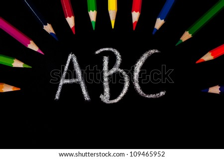 A blackboard with colored crayons and the letters A, B and C - stock photo