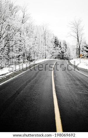 A blacktop country road during the winter with snow all around. - stock photo