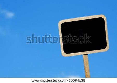 a blank blackboard label over the blue sky - stock photo